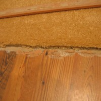 Floating Laminate Floor Has Been Bound By Construction Adhesive & Fasteners (Improper Installation)